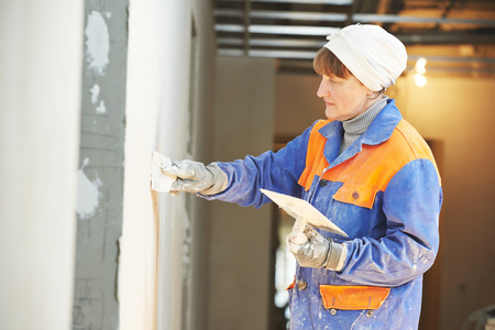 parget: Plasterer at indoor wall renovation stucco decoration with float and plaster