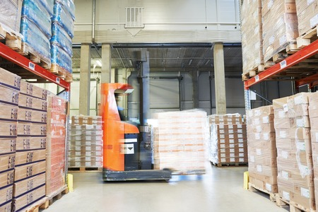 stacker: stacker loader moving goods in a wholesale and retail warehouse Stock Photo