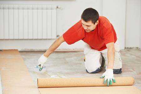 gluing: Worker carpenter doing parquet Wood Floor work gluing down cork padding layer