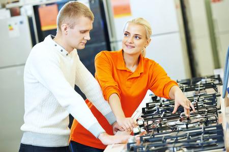 gamme de produit: Jeune homme de gamme Cuisine cuisini�re en choisissant �lectrom�nager centre commercial supermarch�