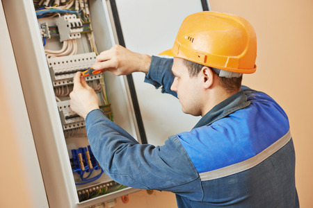 screwing: Young adult electrician builder engineer screwing equipment in fuse box