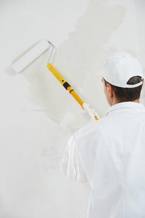 pintor: Una casa masculino trabajador pintor pintura e imprimación de pared con el rodillo de pintura Foto de archivo
