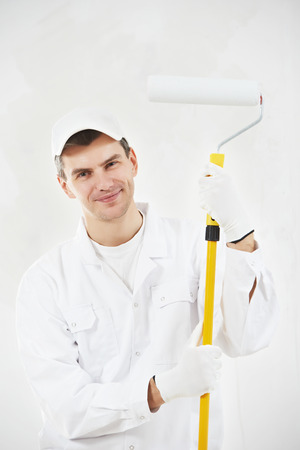 priming paint: Portrait of one male house painter worker with painting roller