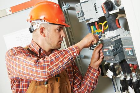 electrician builder engineer screwing equipment in fuse box Foto de archivo