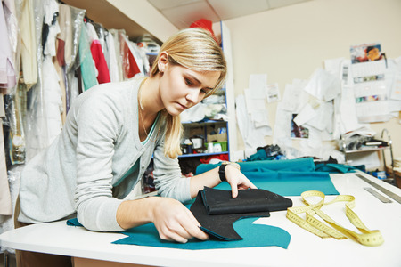 tailor measuring tape: young female tailor working with cloth fabric in workshop Stock Photo