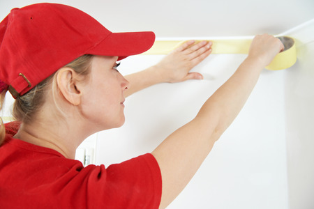 priming paint: Woman painter worker protecting ceiling moulding with masking tape before painting at home improvement work Stock Photo