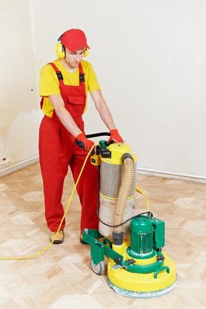 mantenimiento: carpintero haciendo parquet de piso de madera pulido de los trabajos de mantenimiento de la máquina de molienda Foto de archivo