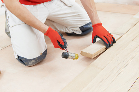 tongue and groove: carpenter worker installing wood parquet board during flooring work with hammer Stock Photo