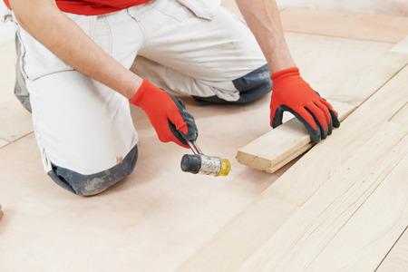carpenter worker installing wood parquet board during flooring work with hammer photo