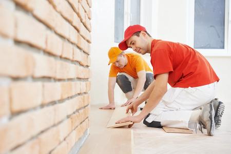 carpintero: Dos trabajadores de la instalaci�n de parquet carpintero tablero de madera durante el trabajo de suelos