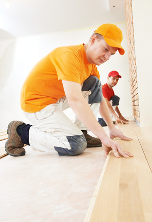 Two parquet carpenter workers installing wood board during flooring work photo