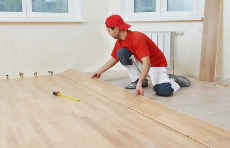 carpenter worker installing wood parquet board during flooring work with hammer Stock Photo