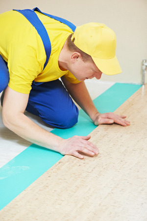 tongue and groove: One carpenter worker laying cork boards during indoors flooring work Stock Photo