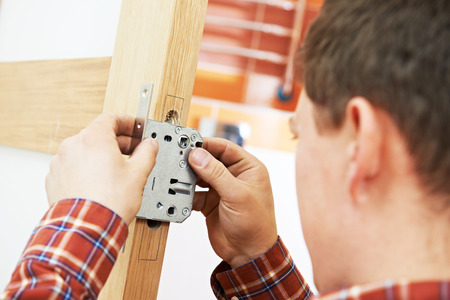 deadbolt: Male handyman carpenter at interior wood door lock installation with angle