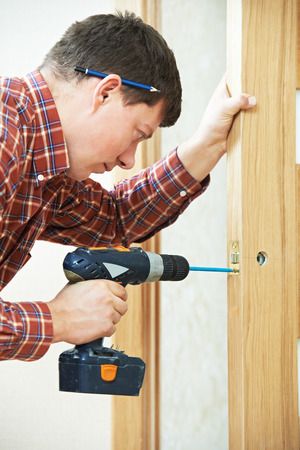 carpenter at lock installation with electric drill into interior wood door photo