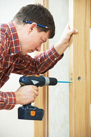 locksmith: carpenter at lock installation with electric drill into interior wood door