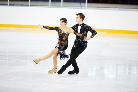 figure skating of young skaters pair at sports arena