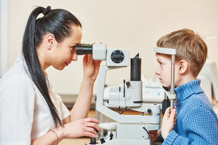 eye test: Optometry concept. Female optometrist optician doctor examines eyesight of child boy in eye ophthalmological clinic