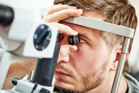eyes: Ophthalmology concept. Male patient under eye vision examination in eyesight ophthalmological correction clinic Stock Photo