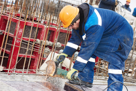 erector: Construction builder worker with grinder machine cutting metal reinforcement rebar rods at building site
