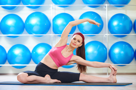 plasticity: fitness, sport, training, gym and wellness. Woman doing stretching excercises in a club