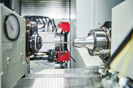 cutting machine is: shaft detail turning on metal cutting machine tool at manufacturing factory Stock Photo