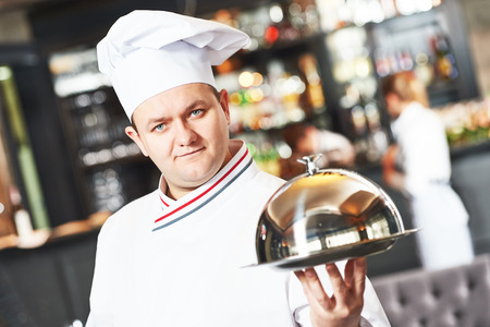 hotel worker: portrait of male cook chef at restaurant serving food with cloche lid