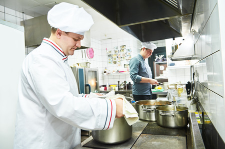 male cooks chef in uniform cooking at restaurant kitchen Stock Photo