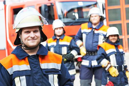 voiture de pompiers: pompier en uniforme devant la machine de camion de pompiers et l'�quipe de pompier