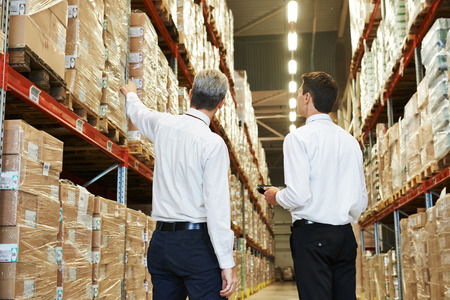 shipping package: two managers workers in warehouse with bar code scanner