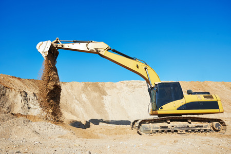 sand quarry: excavator machine doing excavation earthmoving work in sand quarry Stock Photo