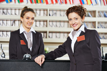 recepcionista: Feliz de pie femenino trabajador recepcionista en el mostrador del hotel