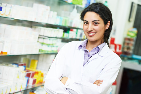 druggist: portrait of cheerful pharmacist chemist woman in pharmacy drugstore