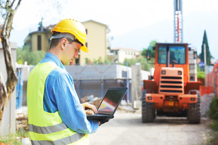 person computer: Bauarbeiter in Schutzarbeitsschutzkleidung mit Laptop-Computer auf der Baustelle vor loader Maschinen