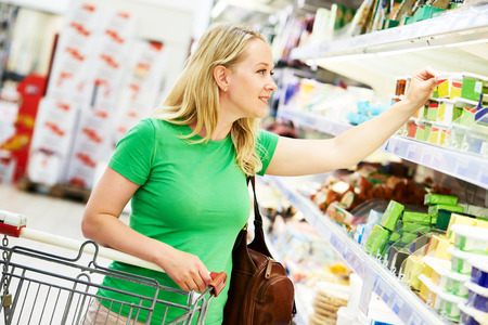 Shopping. Woman choosing bio food cheese products in dairy store or supermarket Stock Photo
