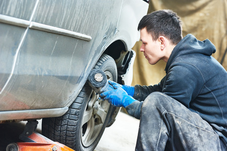 car shop: auto mechanic worker sanding polishing bumper car at automobile repair and renew service station shop by polishing ggrinding machine Stock Photo