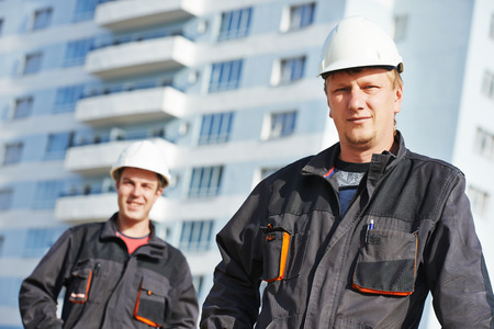 construction crew: Team of smiling foreman builders workers in protective uniform at construction building site Stock Photo