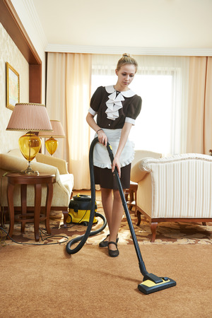 hotel staff: Hotel service. female housekeeping worker with vacuum cleaner in room apartment