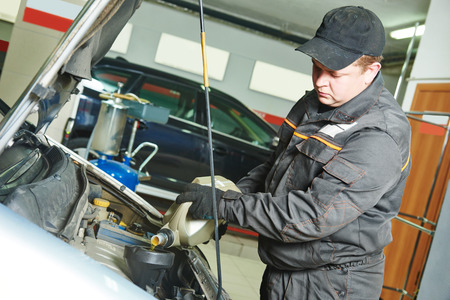 scheduled replacement: auto mechanic technician replacing and pouring motor oil into automobile engine at maintenance repair service station