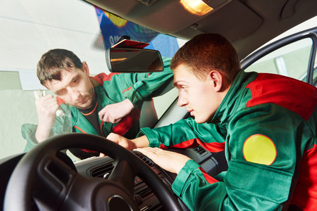 glazier: Automobile glazier repairman teaching or discussing with partner windscreen repair of a car in auto service station garage