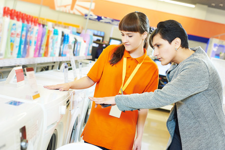 Young female seller assistant helps woman to choose washing machine in home appliance shopping mall supermarket photo