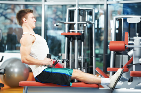 man with training equipment at fitness club gym doing exercises for back muscles photo