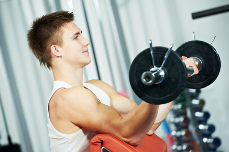 athlete man workout biceps brachii muscles exercises with training weight in fitness gym photo