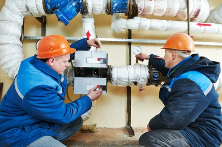 two repairman engineer of fire engineering system or heating system open the valve equipment in a boiler house Stock Photo