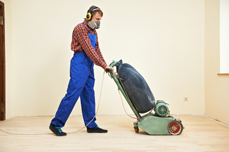 wood flooring: carpenter doing parquet Wood Floor polishing maintenance work by grinding machine Stock Photo