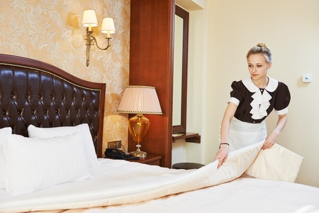Hotel service. female housekeeping worker maid making bed with bedclothes at inn room Stock Photo