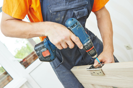 carpintero: carpintero en la puerta interior de madera instalaci�n de la cerradura de trabajo con un destornillador