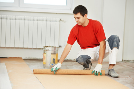 padding: Worker carpenter doing parquet Wood Floor work gluing down cork padding layer