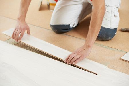 carpintero: Trabajador que instala el carpintero o el piso de parquet de reparación en la capa de suelo de corcho Foto de archivo