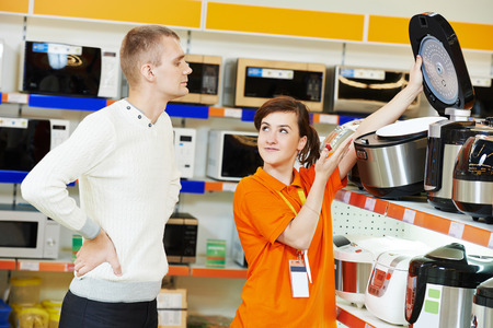 oven range: Young man choosing electric oven in home appliance shopping mall supermarket Stock Photo